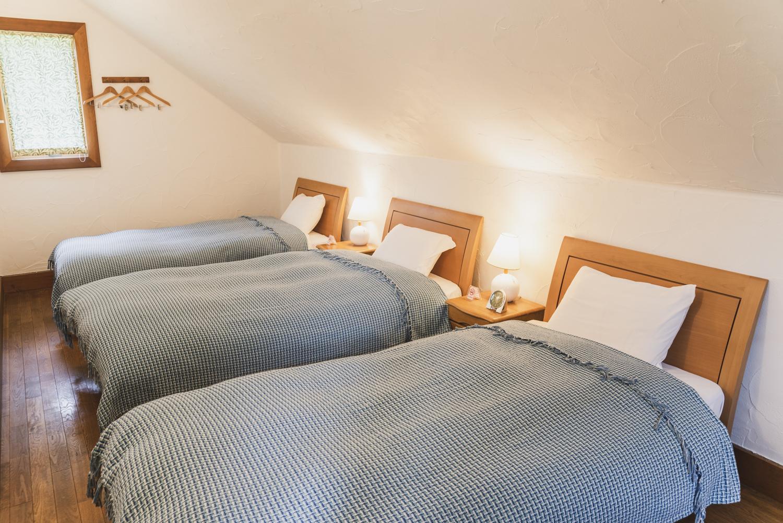 バウムコレクション コテージAベッド3台とエキストラベッドがある寝室